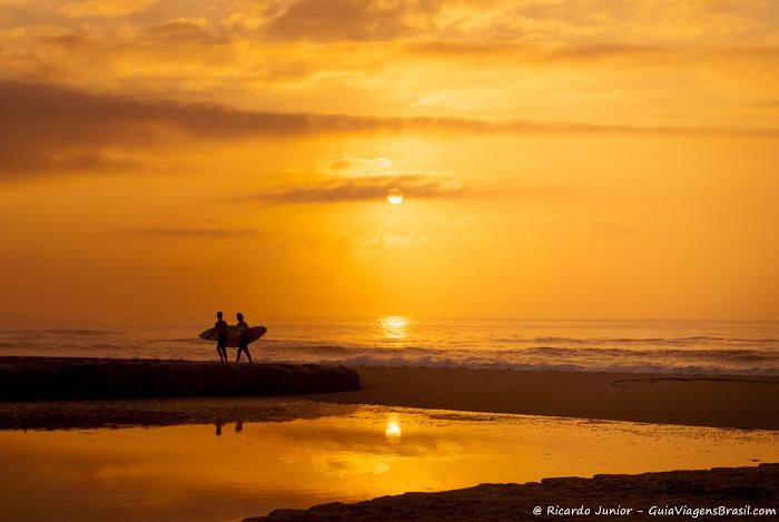 Imagem de surfistas caminhando na Praia Brava de Itajaí com belo pôr do sol ao fundo.- Photograph by Ricardo Junior / www.ricardojuniorfotografias.com.br