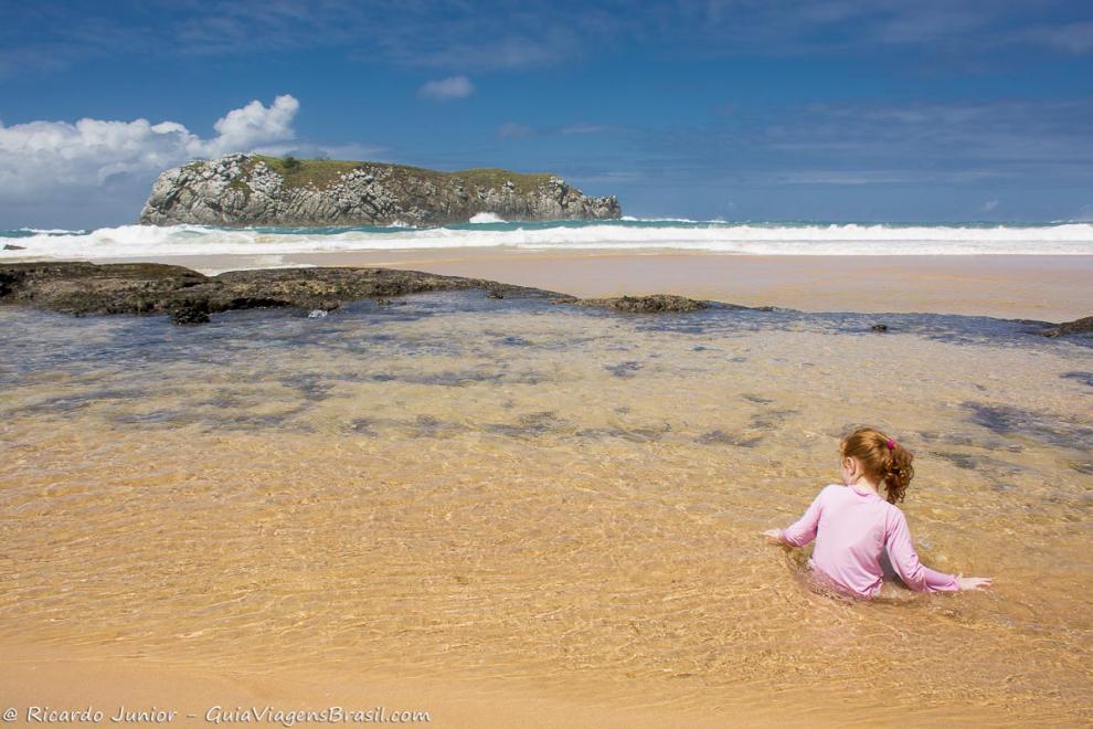 imagem-de-uma-crianca-sentada-na-beira-do-mar-brincando-fernando-de-noronha-pernambuco