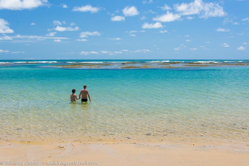 imagem-de-duas-pessoas-com-aguas-claras-pela-cintura-na-praia-taipu-de-fora-bahia-ba