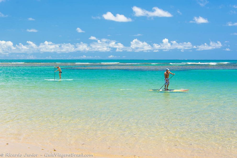 Imagem de duas pessoas praticando stand up paddle-Praia Taipu de Fora-Bahia-BA