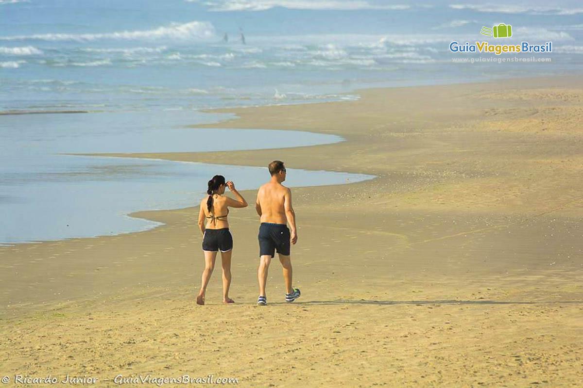 Imagem de casal caminhando na Praia do Luz, Imbituba, SC.