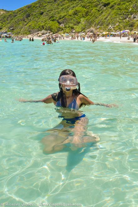 Foto menina mergulhando na Praia do Pontal do Atalaia, em Arraial do Cabo, RJ.