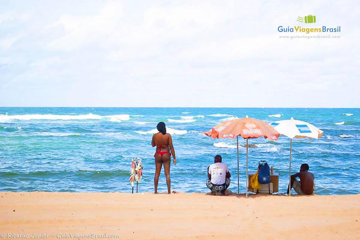 Foto de turistas olhando o mar na Praia de Itapuã, Salvador.