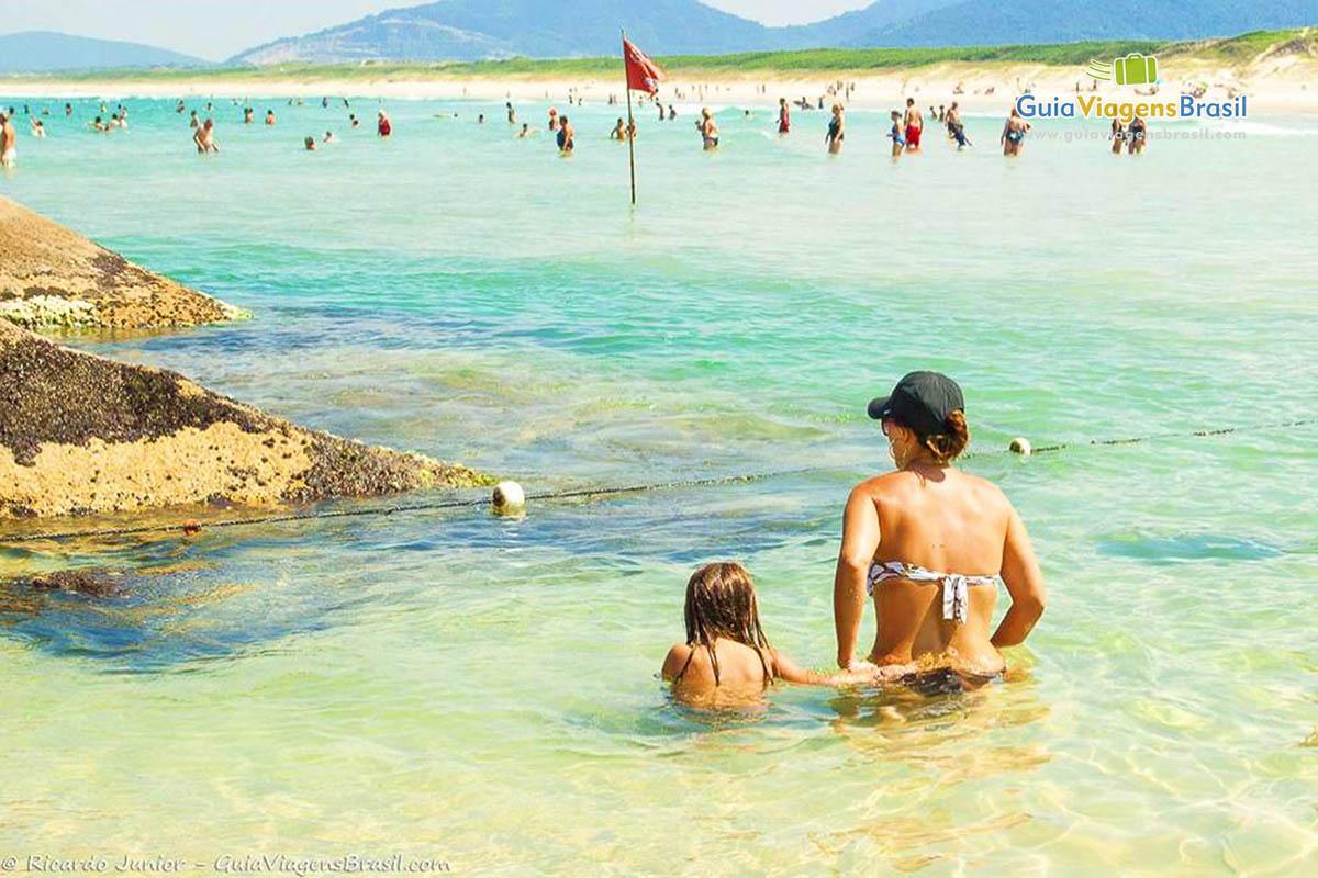 Foto de mãe e filha entrando no mar na Praia da Joaquina.