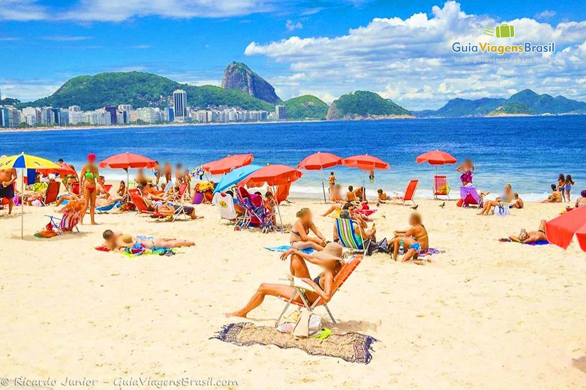 Foto turistas curtindo dia de sol na Praia de Copacabana, Rio de Janeiro, RJ.