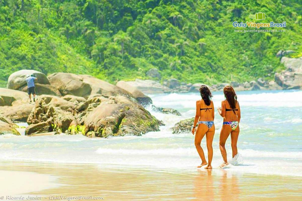 Foto mulheres caminham na Praia de Mariscal, Bombinhas, SC.