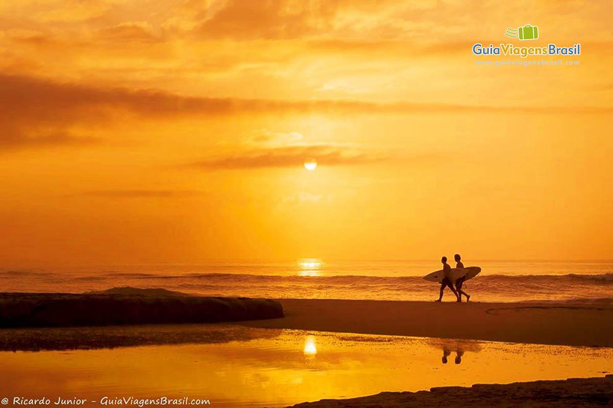 Foto surfistas ao pôr do sol na Praia Brava, Itajaí, SC.