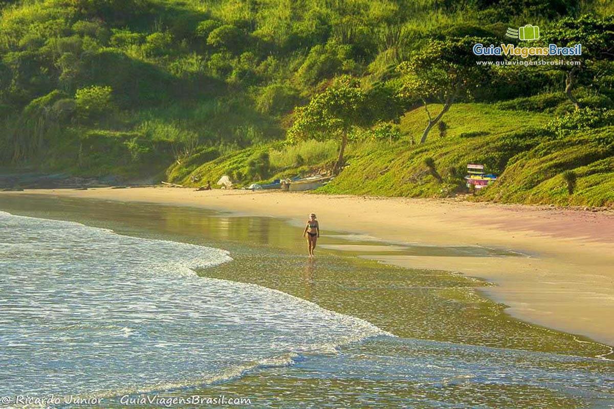Foto pessoa caminhando na água da Praia Brava, em Búzios, RJ.
