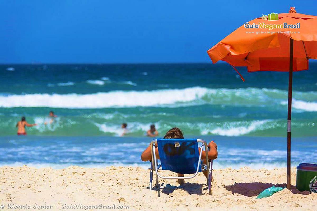 Foto turista e mar na Praia do Campeche, Florianópolis, SC.