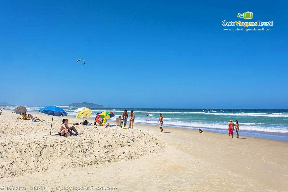 Foto turistas na orla da Praia do Campeche, Florianópolis, SC.