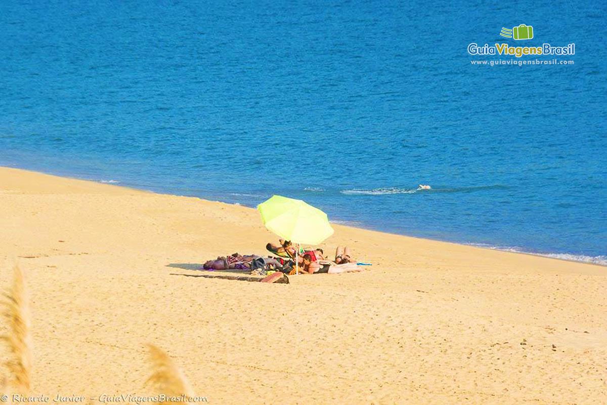 Foto do mar calmo e a areia clara da Praia de Boiçucanga, em São Sebastião, SP.