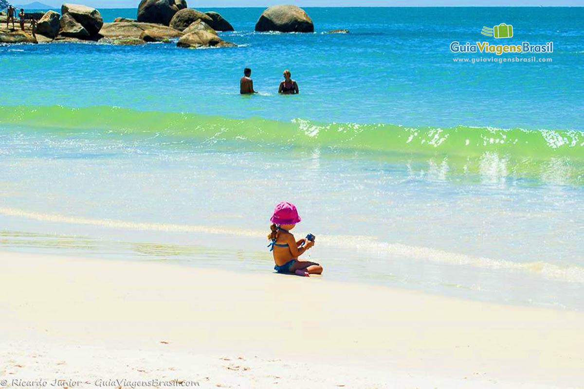 Foto criança brincando na Praia de Bombinhas, SC.