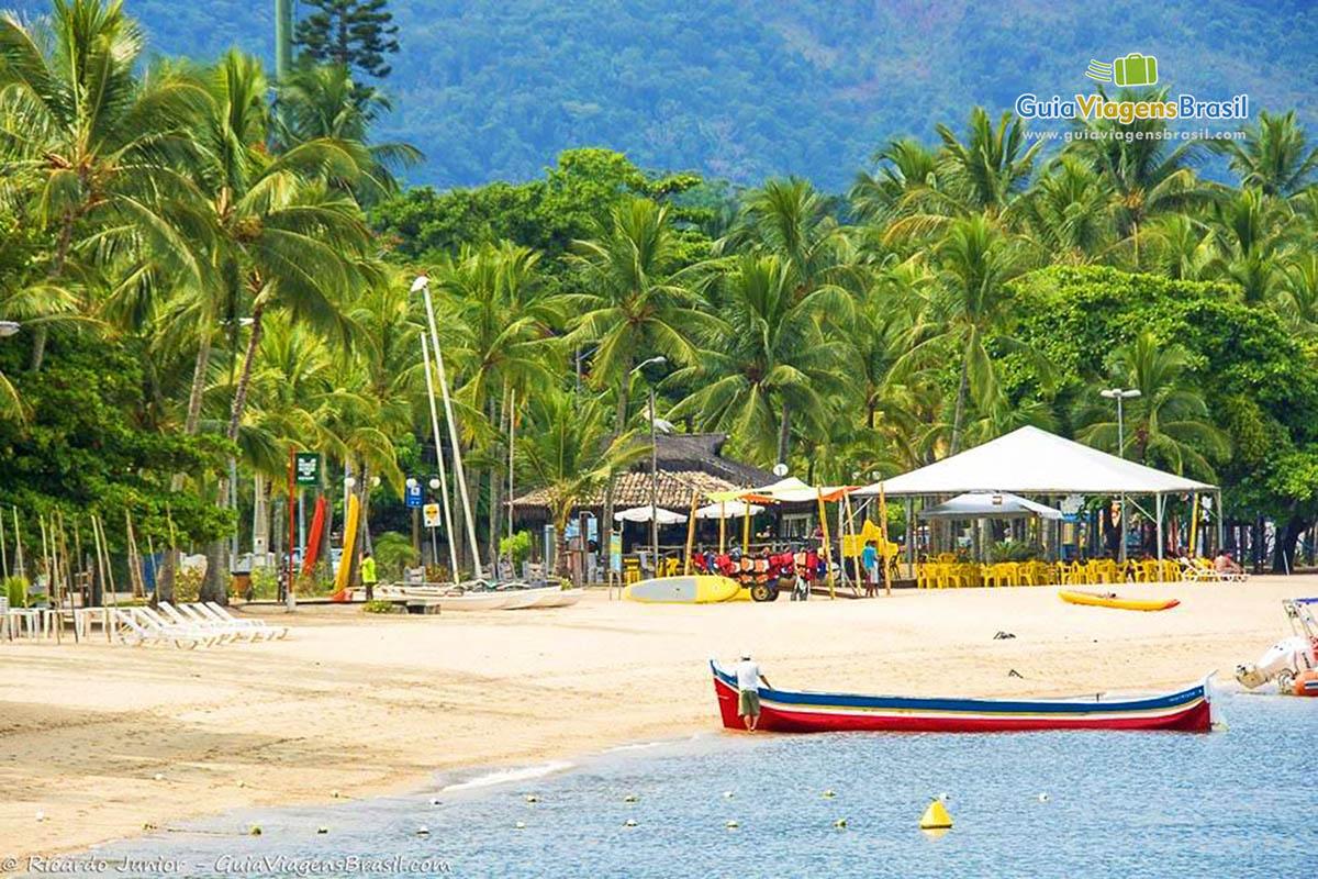 Foto da orla com barco na Praia de Perequê, em Ilhabela, SP.