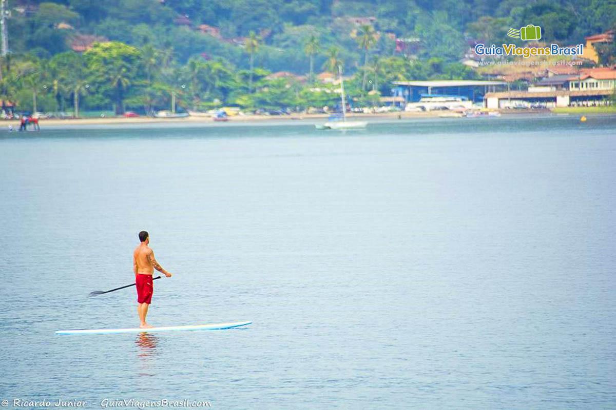 Foto praticante de stand-up-padlle na Praia de Perequê, em Ilhabela, SP.