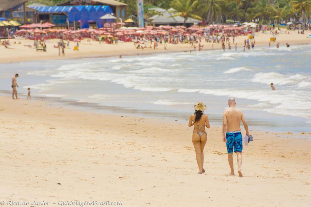 Imagem de um casal andando na beira do mar da Praia de Itacimirim.
