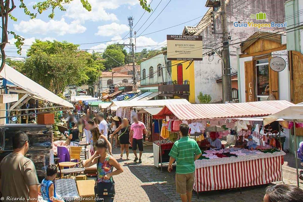 Imagem das barracas nas ruas de paralelepípedos de Embu das Artes. #6D4232 1200x800
